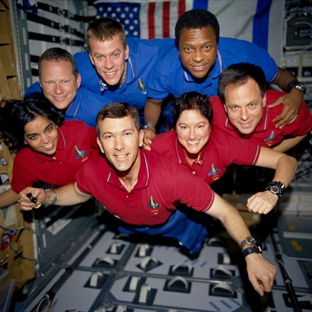 STS-107 crewmembers strike a 'flying' pose for the traditional in-flight crew portrait aboard the Space Shuttle Columbia. Rick D. Husband, mission commander, is pictured in the center foreground wearing his X-33. On February 1, 2003, the seven crewmembers were lost with the Space Shuttle Columbia over North Texas. This picture was on a roll of unprocessed film later recovered by searchers from the debris on the ground. Godspeed, Columbia. Photograph courtesy of NASA archives.
