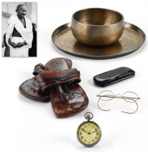 Antiquourm Lot #364 in the March 4-5 Auction: Zenith Alarm Pocketwatch, Eyeglasses, and Sandals described as having been owned by Mohandas Gandhi.  Photo: Antiquorum.